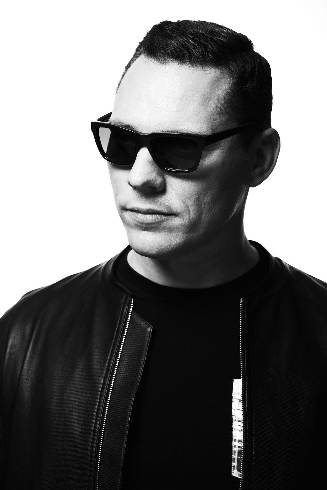 Tiësto wears a jacket by Alexander Wang, t-shirt by Mugler, jeans by Balmain, sunglasses by Giorgio Armani