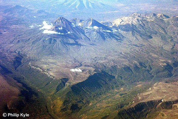 Le Groupe volcanique Gamchen : De gauche à droite : les quatre sommets du volcan Gamchen, le sommet jaunâtre du Komarov, composé de roches altérées hydrothermalement, et à l'extrême droite, le Vysoky. - photo Philip Kyle / KSCNET