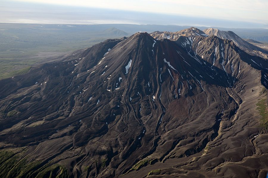 The volcano Kikhpinych - in the foreground , the cone Savich and recent lava flows . - Photo I.Shpilenok