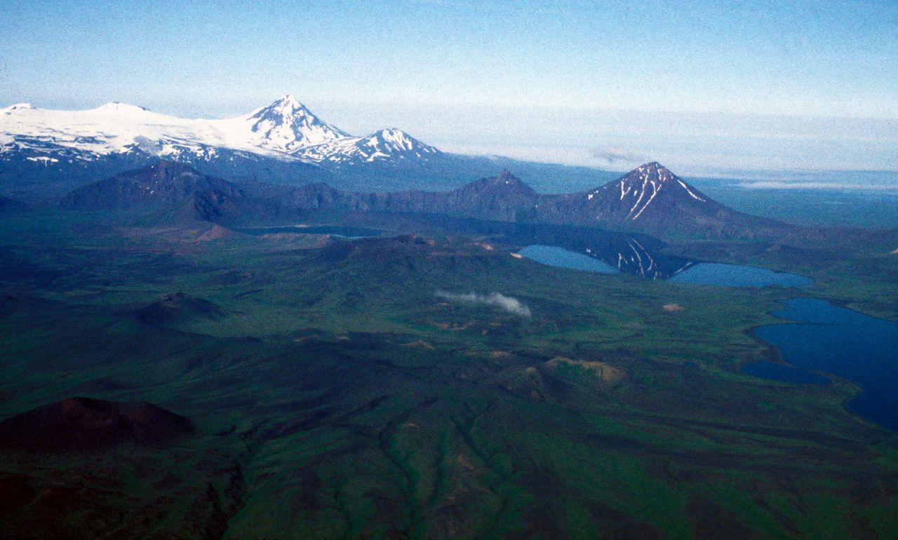 In the foreground, the Fisher caldera , with its rims not covered with snow, and left the Mt. Finch - In the left background, the snow-capped peaks , from left to right : Westdahl , Faris Peak, the Progromni and Pogromni sister - photo Peter Stellling 1998 / AVO - USGS
