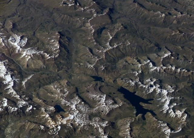 In this photo of the ISS, the volcanic complex Domuyo area is covered with snow, located in the upper left corner. The elongate Laguna Valvarco, bottom right, sits near the western edge of the caldera Valvarco, dated of Pleistocene. (north is at the bottom right) - photo NASA Space Station image ISS008-E-7432, 2003