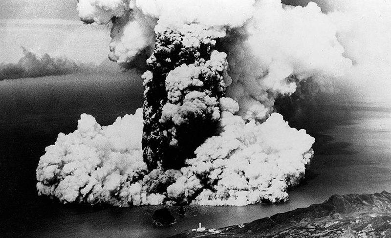 Faial - Eruption du Capelinhos 1957 -  panache et base surges &#x3B; l'échelle est donnée par le phare à l'avant-plan - Espólio do T. C. José Agostinho- Museu de Angra do Heroísmo / Siaram