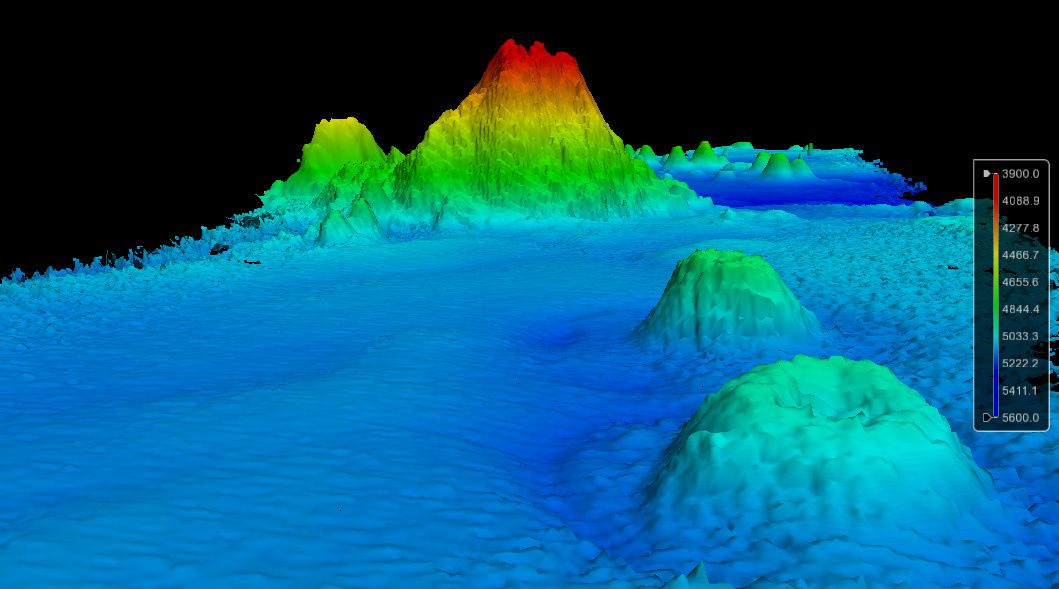 La zone d'investigation : à l'avant-plan droit, deux volcans - en arrière-plan, le nouveau seamount - 3D view of the seamount area (SE point of view and 3.5x vertical exaggeration)  - doc CCOM/JHC / http://ccom.unh.edu/seamount-discovery-2014