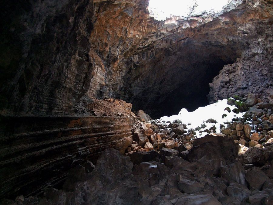 El Malpais NM / Big Skylighy cave - Boulders and a pile of snow remaining illuminated by a skylight - photo American southwest