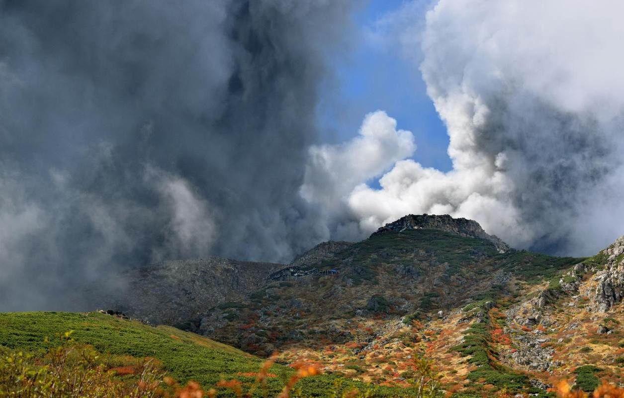 Ontake - éruption du 27.09.2014 - le nuage de cendres engloutit les pentes du volcan encore partiellement aux couleurs d'automne - photo d'un anonyme / via Kyodo news
