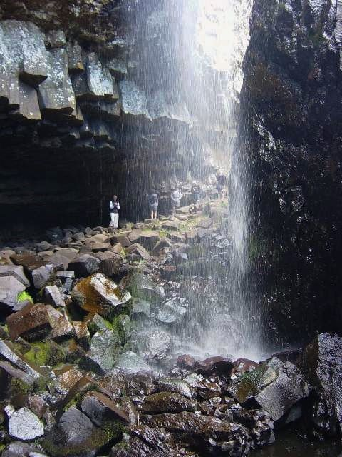 Waterfall of Déroc - Erosion continues his work and large pieces of organs littering the floor of the shelter - visitors for scale - photo Terres & Civilizations
