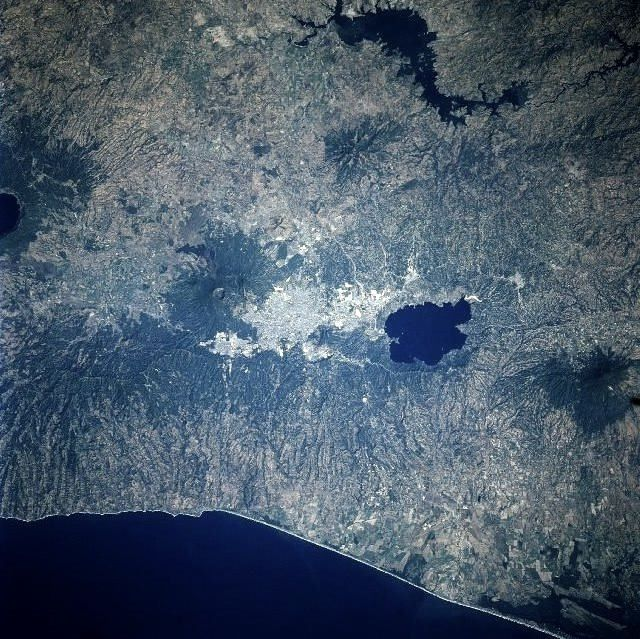 Seen from space, the city of San Salvador and Lake Ilopango - with the Ilopango volcano on the right, left San Salvador volcano and the Loma caldera on the far left. - Photo Nasa.