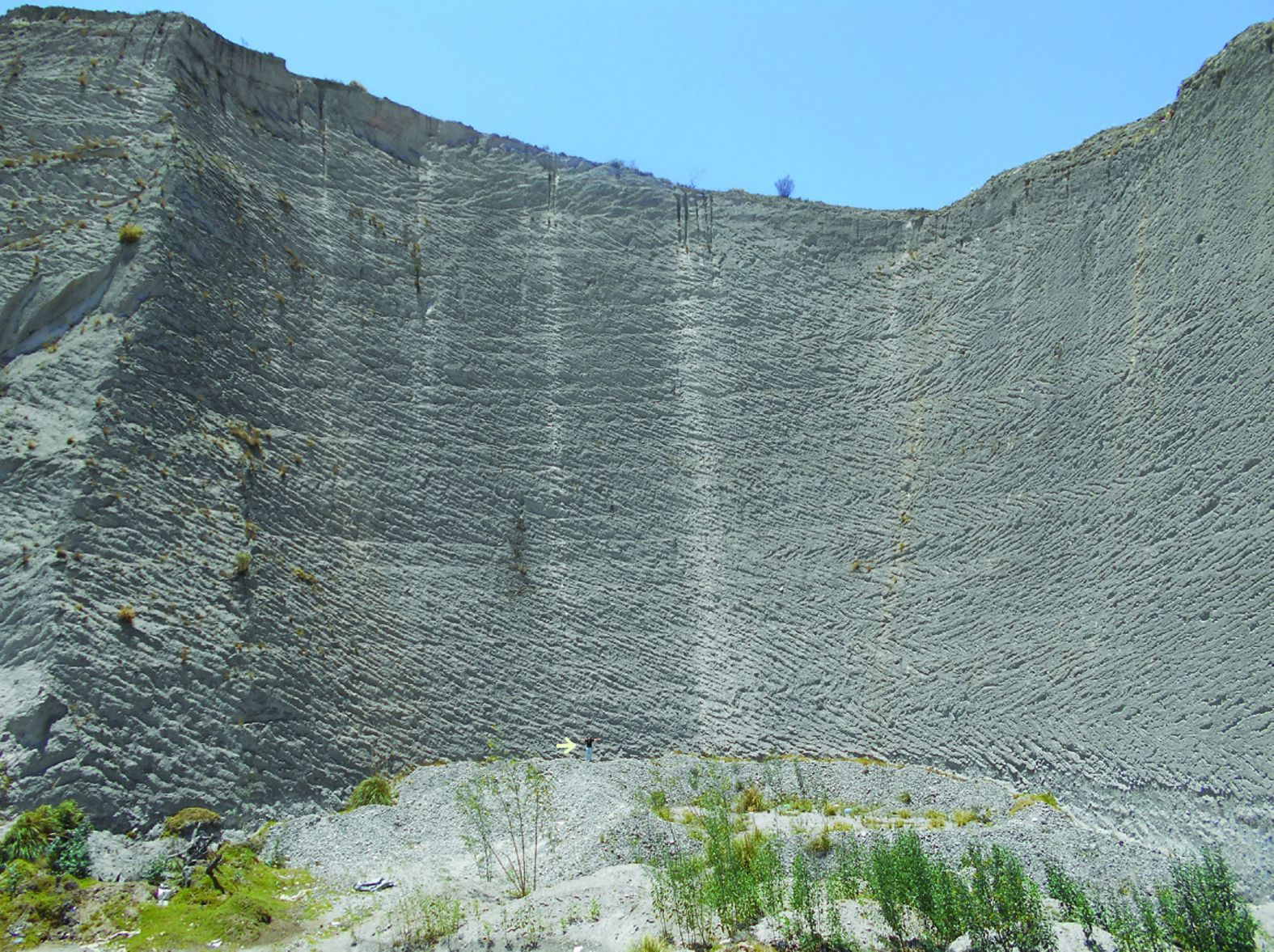 Ignimbrite deposits, up to 56 meters, from the final eruptive phase of Chalupas volcano, located 31 km SW of the caldera - the scale is given by the man (arrow at the base of the deposit) - Cortesía GEO1 - Theofilos Toulkeridis