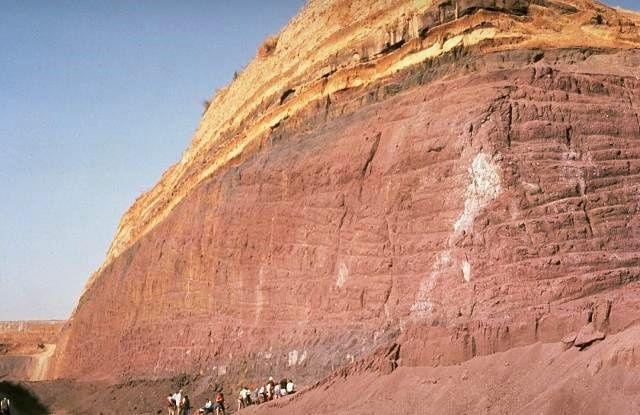 Geologists examine a quarry in a post-caldera cone of the Vulsini volcanic complex. The base of the quarry exposes thick, red-colored scoria deposits produced by strombolian eruptions that built a cinder cone. These are overlain by bedded, yellowish pyroclastic-surge deposits.  Photo by Richard Waitt, 1985 (U.S. Geological Survey).