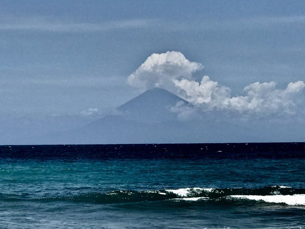 Agung surmounted by a steam plume on 19.10.2017, seen from Lombok, the neighboring island - the small plume blends quickly with the clouds - photo Moo / Twitter