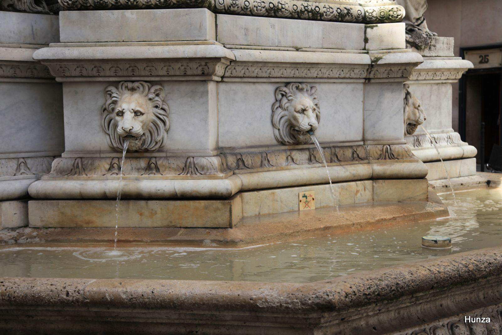 Trois mascarons à tête de lion crachent l'eau dans une vasque
