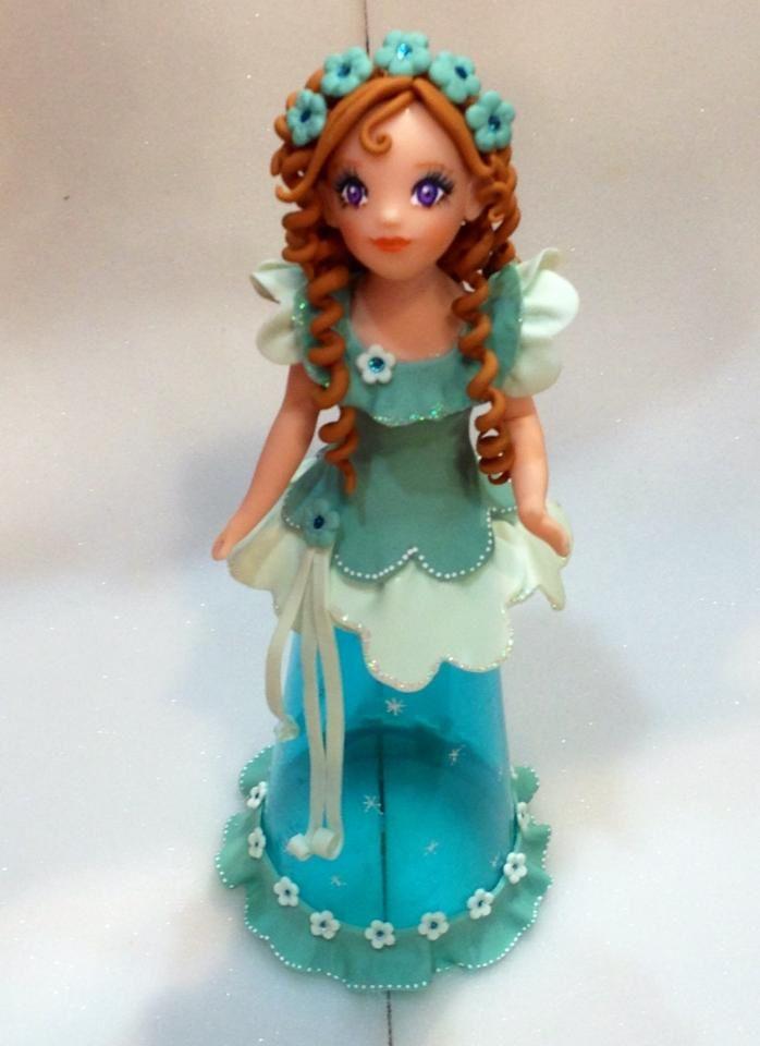 Princesse sur coupe à champagne en plastique ! Mélange de bleu azur et de vert pour la robe, amande pour la basque et les rubans