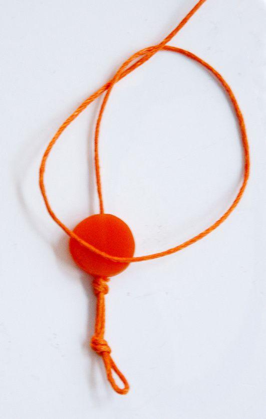 Ich lege die Schnur um die Perle zu einer Knotenschlaufe. Die Schlaufe sollte möglichst nah an der Perle sein. Als Gedankenstütze lege ich die Kordel vor die Perle, so dass ich in die Schlaufe hineinkucken kann.
