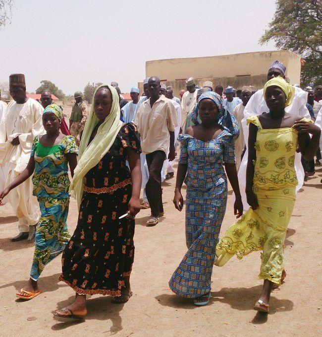 En ce lundi 21 Avril, 2014 photo d'archives, quatre étudiantes de l'école secondaire publique Chibok, qui ont été enlevées par des hommes armés et on pu rejoindre leur famille marchent à à pied dans Chibok, Nigeria. Un groupe de la société civile a dit le mercredi 30 Avril 2014, que des villageois rapportent que des dizaines de filles et de jeunes femmes qui ont été récemment enlevées d'une école au Nigéria sont contraintes d'épouser des extrémistes islamiques. Un sénateur fédéral de la région, dans le nord du Nigeria presse le gouvernement d'obtenir une aide internationale pour sauver les plus de 200 filles manquantes enlevées par Boko Haram il y a deux semaines. (AP Photo / Haruna Umar, File))