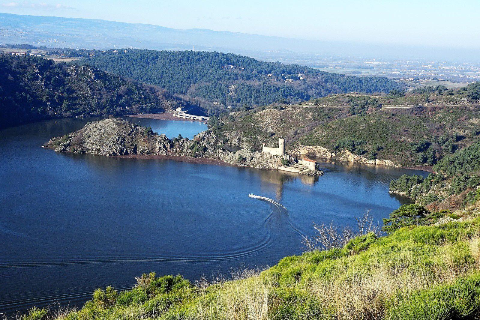 Vue sur le barrage et la presqu'île, un bateau s'amuse à faire des ronds dans l'eau.