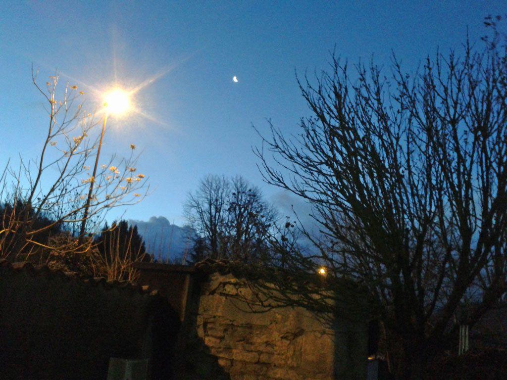 Ciel du 5 décembre à 8 H 15... On aperçoit un bourgeonnement de nuages gris sombre, au Sud Est où un croissant  de lune  flirt avec la lumière du lampadaire...