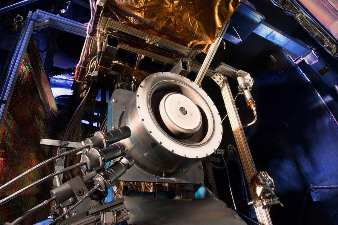 Un propulseur Hall de haute puissance vu à l'intérieur d'une chambre de test au Glenn Research Center de la NASA.