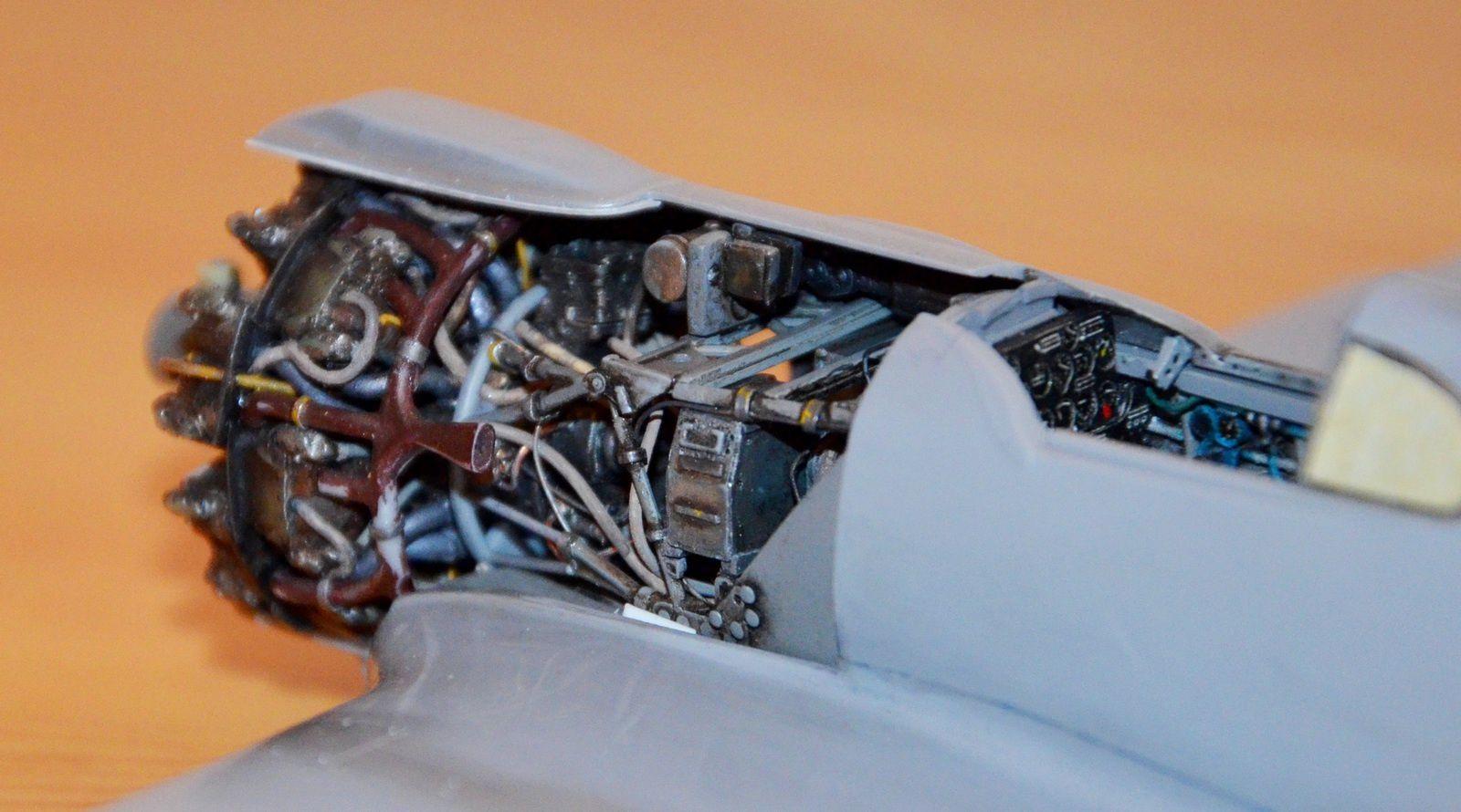 Vue de l'échappement creusé (photo de gauche) et de la petite tôle en carte plastique ajoutée et dépassant autour du coté gauche du corps de prise d'air frontale (en blanc sur la photo).