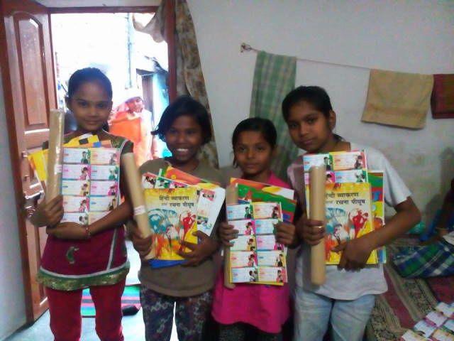 Distribution des livres et des cahiers chez Vivek : Anjali, Punam, Vandana et Chinki.