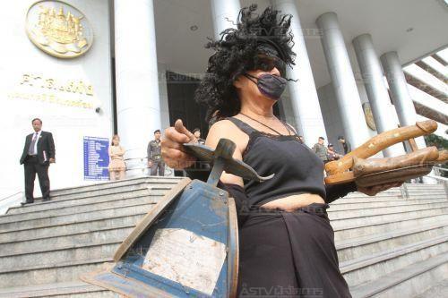 Une femme caricaturant Madame Justice en face de l'édifice de la Cour de justice. Sa main gauche tient un talisman palad-khik, une image de pénis en bois