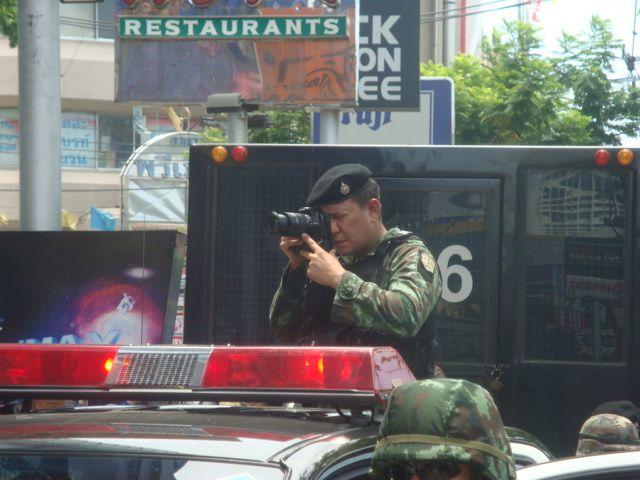Un militaire prend en photo des manifestants pro-démocratie