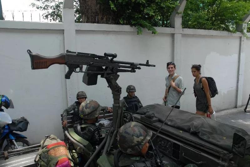 Des touristes passant devant un check point de l'armée