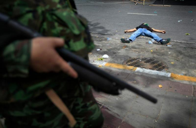 Un soldat armé devant un manifestant assassiné en 2010