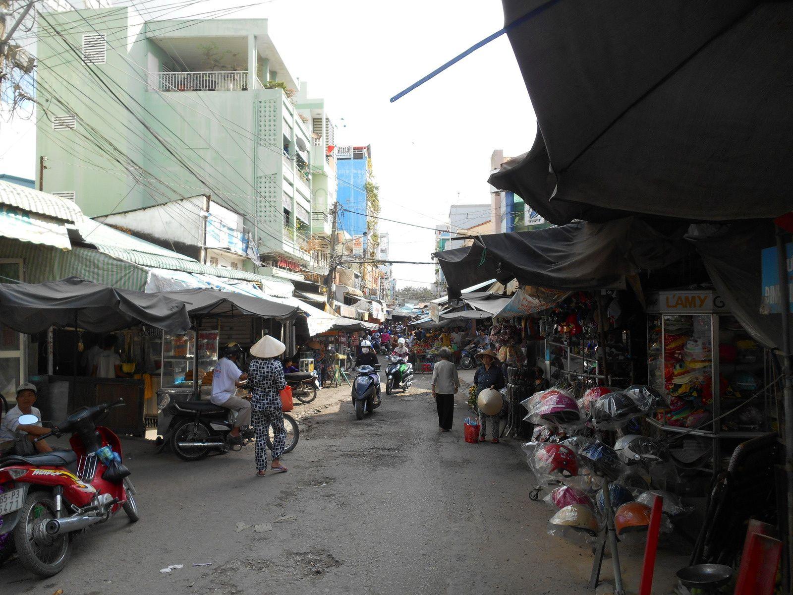Rue principale du marché où se croisent piétons, mobylettes, vélos...