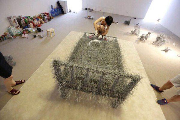 Une artiste chinoise dort nue sur un lit de fils de fer