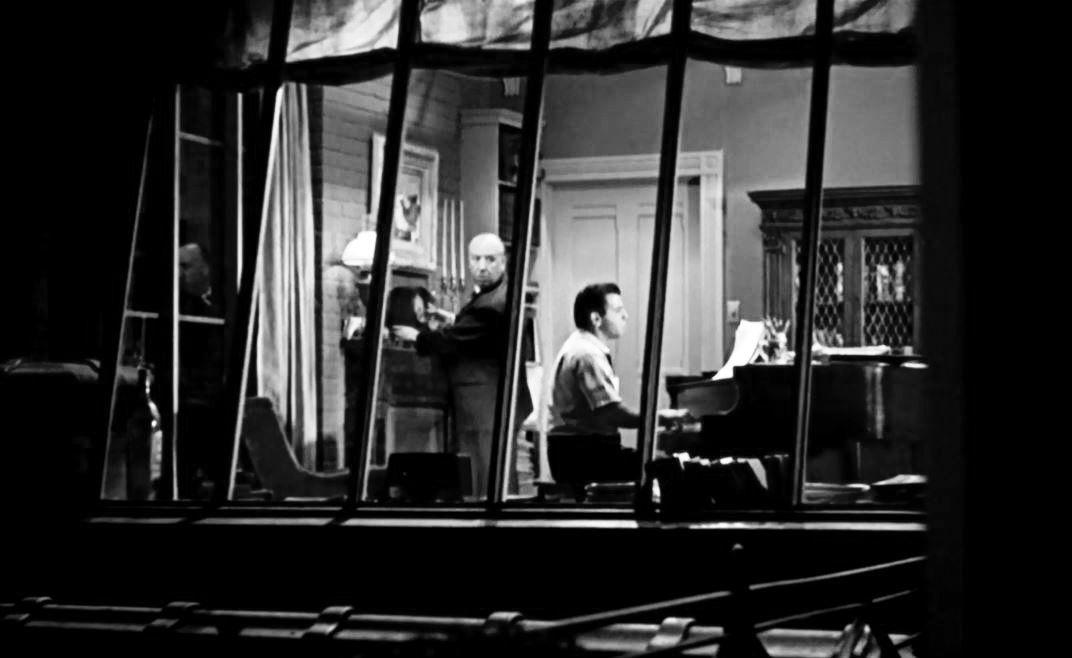 Apparition d'Hitchcock. Dans l'extrait diffué, le compositeur est à sort piano. Derrière lui, un personnage rondouillard remonte une pendule avant de se retourner vers la caméra, révélant le visage d'Hitchcock.