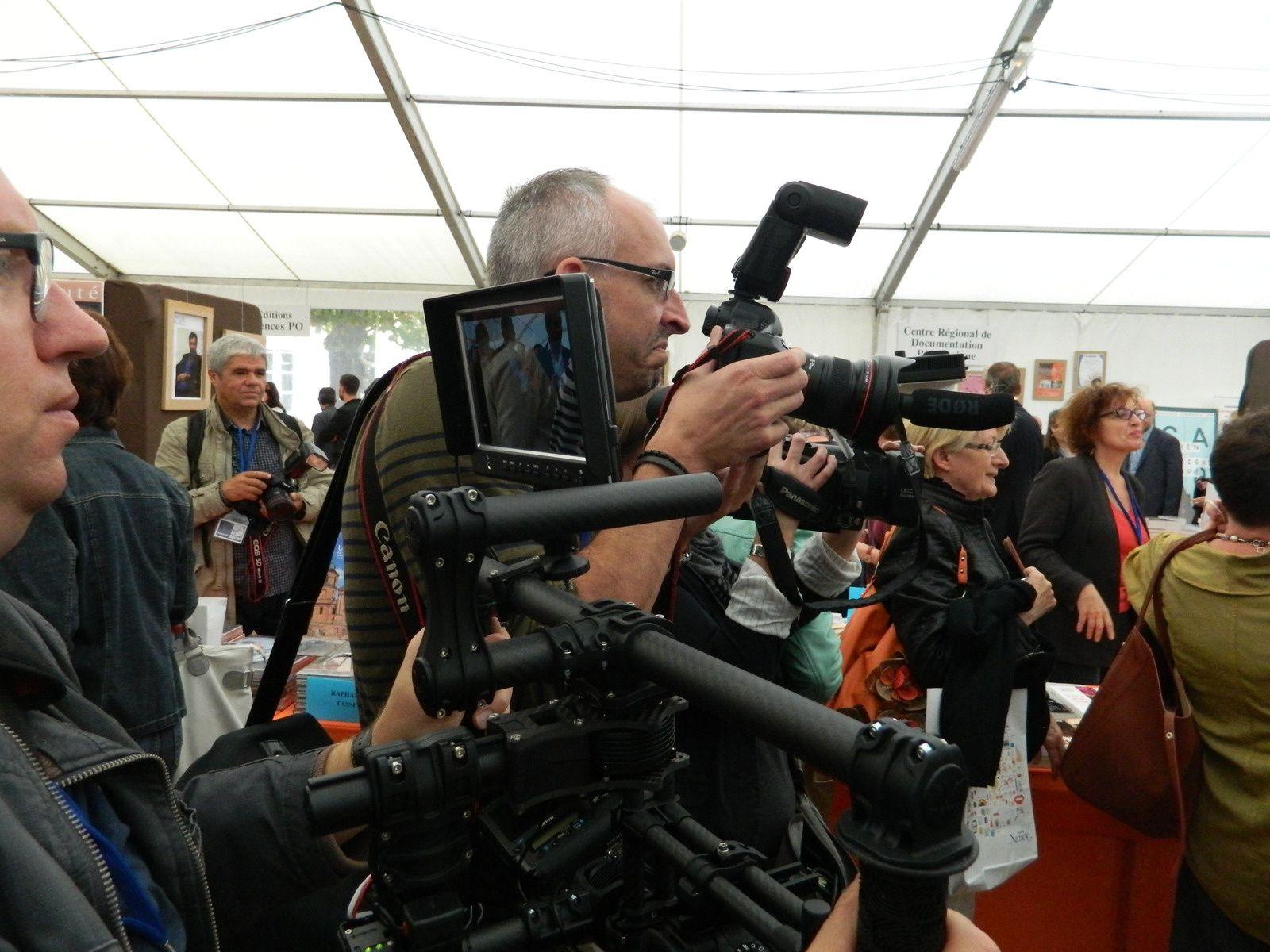 Comme autant d'insectes noirs et peopelivores, les photographes de presse devant le staf du Salon