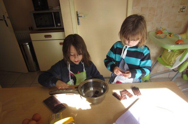 On commence par casser 300g de chocolat noir en morceaux (ici mes filles sont concentrées et attendent qu'une chose un moment d'inattention de ma part et 3/4 morceaux en moins dans la recette !!!)