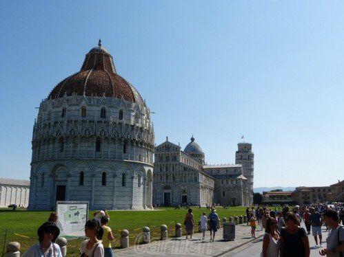 Le Baptistère de Pise  Le premier bâtiment en arrivant du Sud est le baptistère Saint-Jean de Pise (Battistero di San Giovanni). Ce grand cylindre est entouré d'arcades sur colonnes, et est construit en marbre blanc bordé de gris. Sa construction a commencé  en 1153 et s'est achevée non sans mal en 1363.