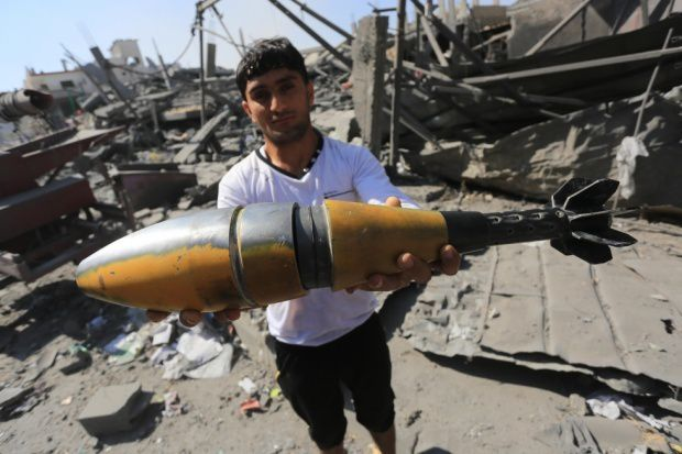 A Palestinian man holding an unexploded ammunition in the Gaza Strip on 1 August, 2014 (MEE/Mohammed Asad)