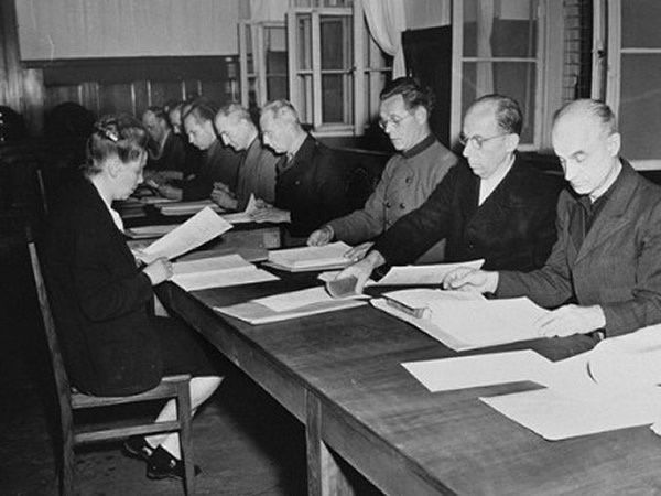 Some of the 14 defendants in the RuSHA Trial at Nuremberg read the indictments against them in July 1947