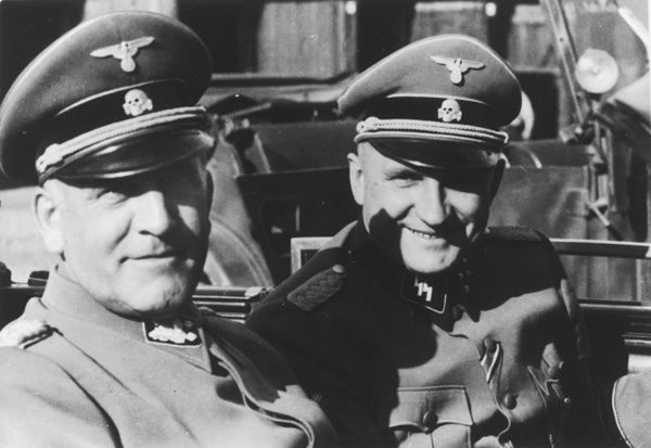 Commandant Richard Baer (right) accompanies Oswald Pohl (left) during an official visit to Auschwitz by automobile.
