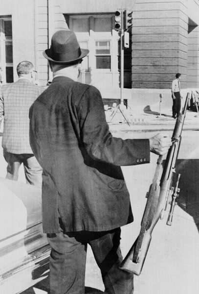 An unidentified plainclothes police officer carries the rifle used in the assassination of President John F. Kennedy in Dallas, Tex., in this Nov. 22, 1963 file photo.