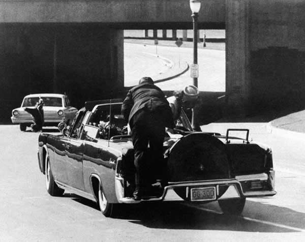 President John F. Kennedy slumps down in the back seat of the presidential limousine after being fatally shot in Dallas on Nov. 22, 1963. Jacqueline Kennedy leans over the president while Secret Service agent Clint Hill, who raced forward after the gunshots, stands on the bumper.
