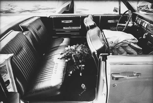 View of flowers on the backseat of Vice-President Lyndon Johnson's Lincoln convertible as it sits parked near the entrance of Parkland Hospital, Dallas, Texas, November 22, 1963. Johnson's car was two lengths behind the car in which President Kennedy was assassinated; after the shooting, the entire motorcade was driven to the hospital, where Kennedy was pronounced dead.