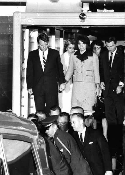 Jacqueline Kennedy, her dress stained with blood, stands with Attorney General Robert F. Kennedy, holding her hand, as they watch the casket of her slain husband, President John F. Kennedy, placed in an ambulance at Andrews Air Force Base, Md., late on Nov. 22, 1963.