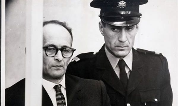 Jerusalem, 1961: Adolf Eichmann listens to the reading of a 15 count indictment as a guard looks on