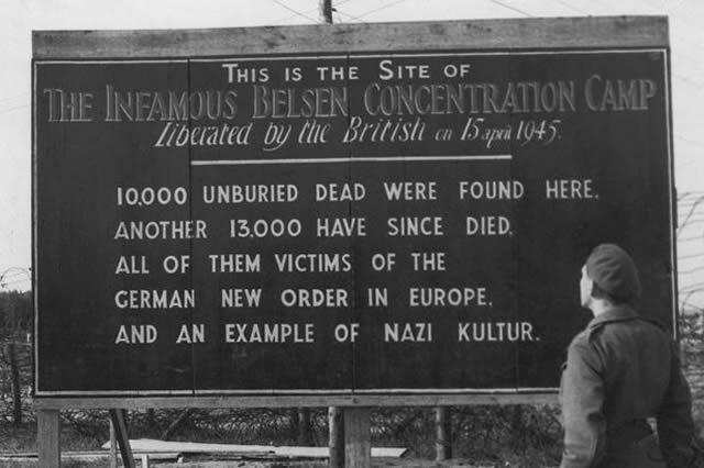 British soldier reads Allied sign detailing horror at camp