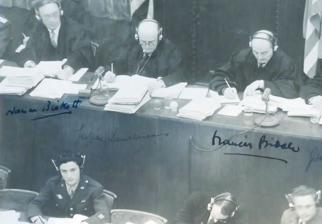 George Sakheim at left, in front of judges at Nuremberg Trial, 1946. The photo was signed by British and American judges