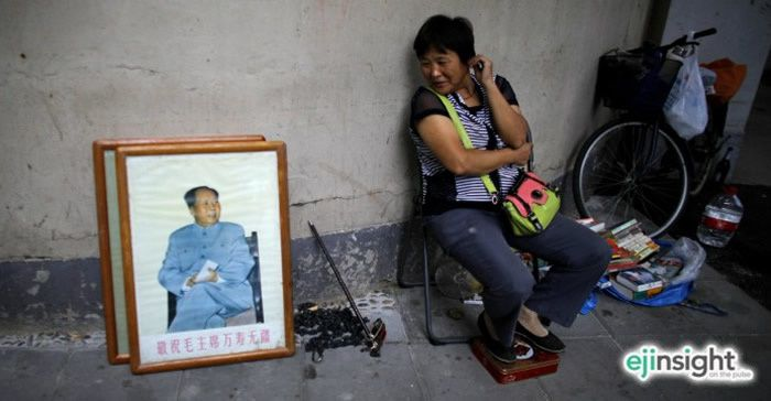 A woman admires a photo of Mao Zedong. Mao once boasted that Qinshihuang, who burried 460 intellectuals alive, was nothing compared to him