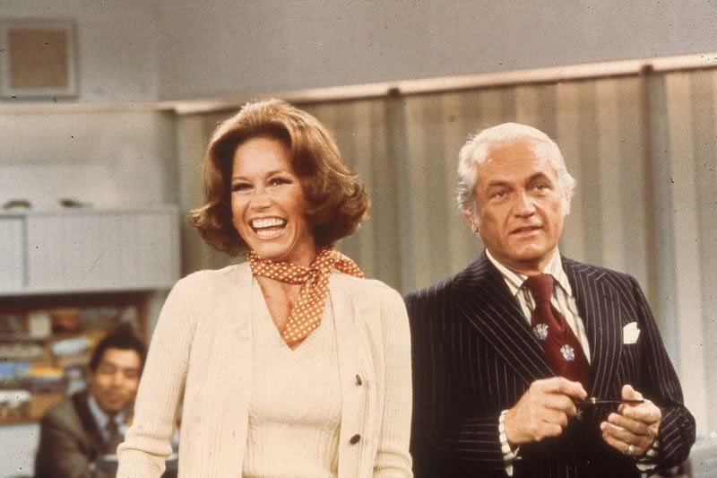 Actors Mary Tyler Moore and Ted Knight laugh in a still from The Mary Tyler Moore Show in 1976
