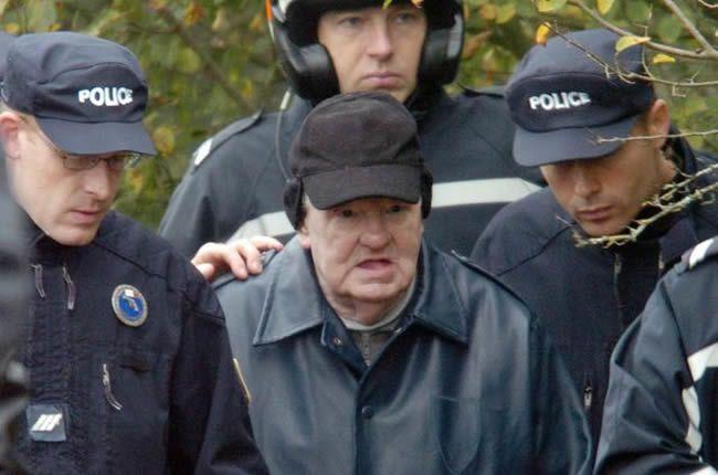 Emile Louis escorté par la police le 10 novembre 2004 à Rouvray lors de son procès à l'endroit où les cadavres de deux victimes -Madeleine Dejust et Jacqueline Weis- ont été découverts en 2001. © AFP / Martin Bureau