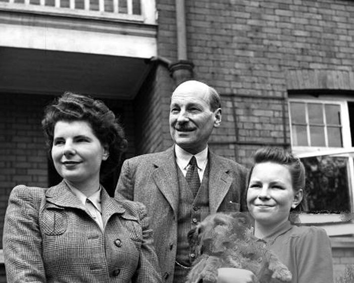 Clement Attlee stands outside his home in Stanmore, with his two daughters (L) Felicity 19, (R) Alison 15 and their dog Ting. 19th April 1945