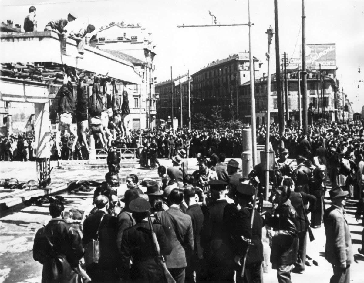 n this April 29, 1945 file photo, dead bodies of fascists hang from the roof at the Piazzale Loreto, Milan, Italy. Benito Mussolini's body is second from left, his mistress Claretta Petacci third from left