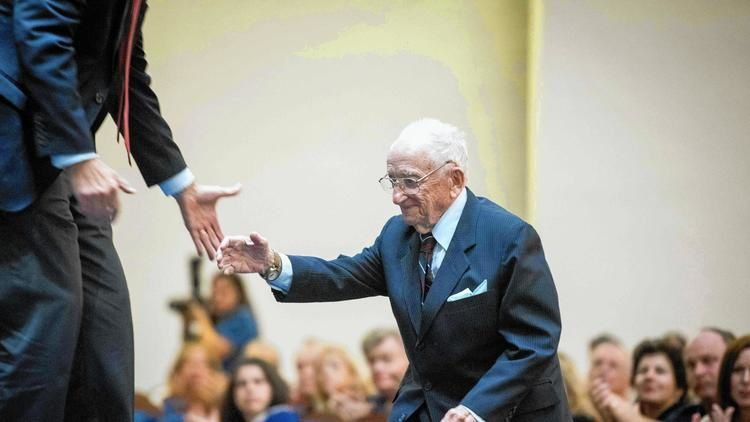 Ben Ferencz, 96, of Delray Beach — the last surviving Nuremberg Trial prosecutor — is helped to the stage as the audience applauds at a speaking engagement on Tuesday, Dec. 13 organized by the USHMM at B'nai Torah Congregation in central Boca Raton. Orit Ben-Ezzer/Staff photographer (Orit Ben-Ezzer / Forum Publishing Group)