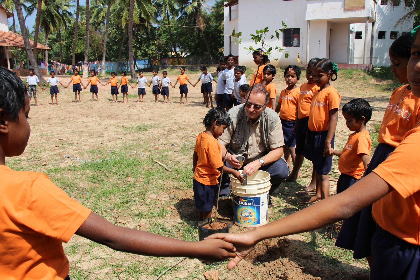 JM en jardinier, aidé des petits et des grands pour planter des neems (margousiers), ces arbres aux vertus médicinales qui soignent tout !